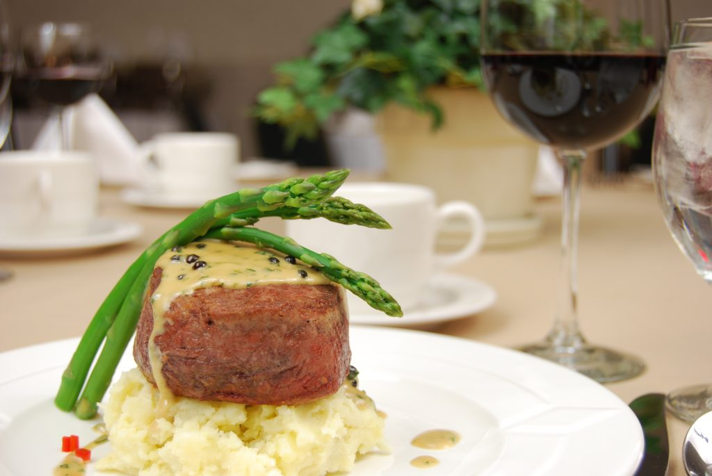Filet mignon over mashed potatoes with asparagus on a restaurant table.